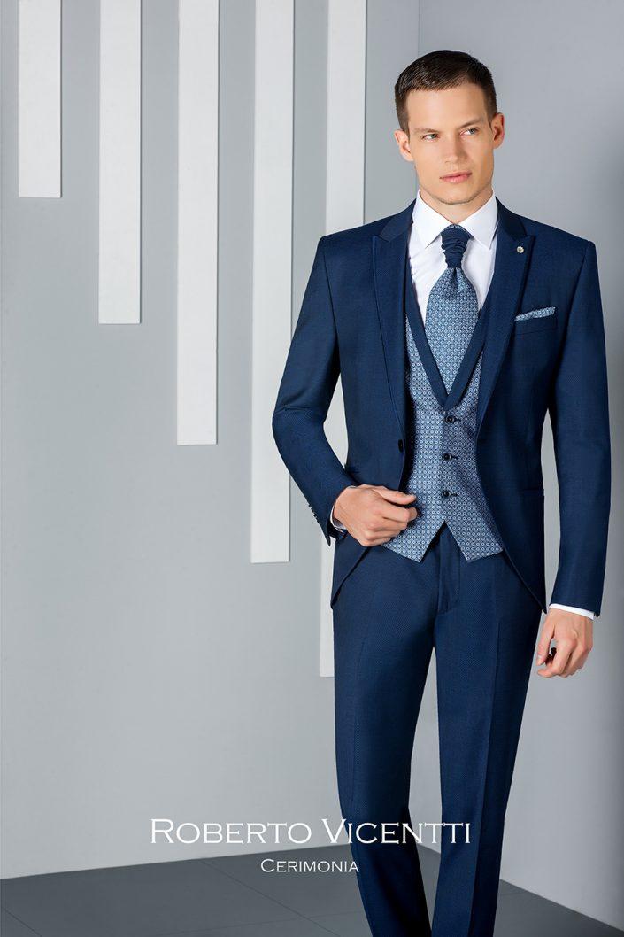 Costume de marié bleu foncé avec gilet bleu clair au motif tissé, chemise et lavallière